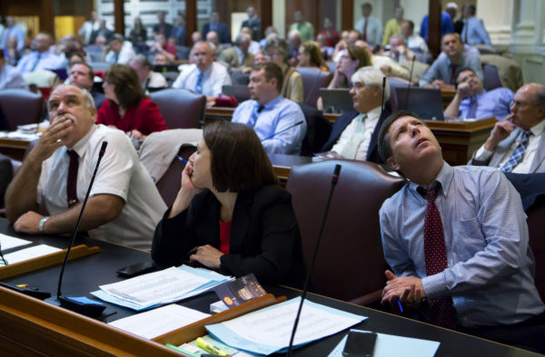 House Minority Leader Ken Fredette (right), R-Newport, watches as votes come in on a vote board during the House of Representatives vote on the state budget at the Maine State House in Augusta.