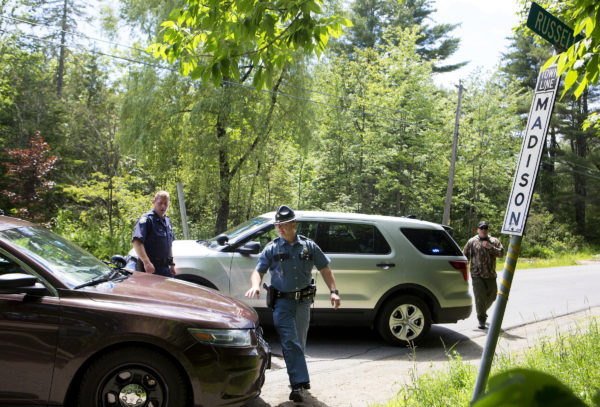 Maine State officers go to their vehicles at a road block on Russell Road in Madison.