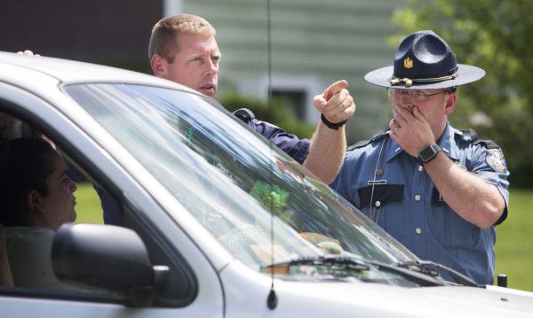 Maine State officers direct a car at a road block on Russell Road in Madison.