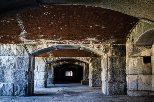 Vaulted brick ceilings, some in need of repair, follow each other in the first course of gun emplacements in Portland's Fort Gorges.