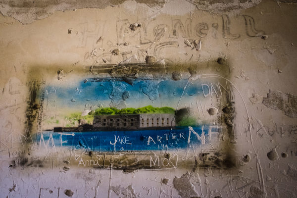 A contemporary painting and graffiti mark the walls in the old officers' quarters inside Portland's Fort Gorges. The fort sits on a ledge in the middle of the harbor.