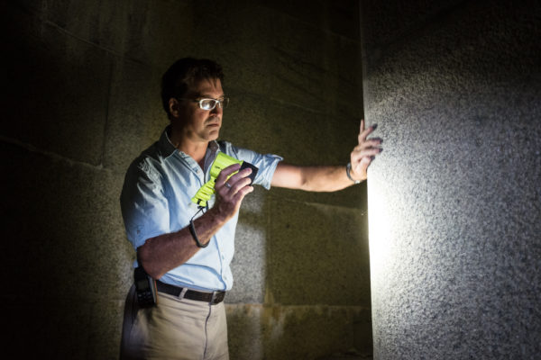 Paul Drinan, executive director of Friends of Fort Gorges, shines a light inside the installation's massive powder magazine. The fort was constructed between 1858 and 1864.