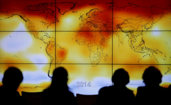 Participants are seen in silhouette as they look at a screen showing a world map with climate anomalies during the World Climate Change Conference 2015 at Le Bourget, near Paris, France, Dec. 8, 2015.