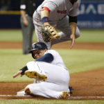Boston first baseman Mitch Moreland misses the ball as Tampa Bay's Logan Morrison slides back into first during the second inning of Thursday's game at Tropicana Field.