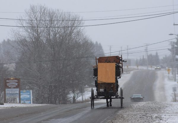 As snow begins to fall, an Amish man in a horse-drawn buggy carrying furniture heads east on Academy Street in Presque Isle in December 2015.