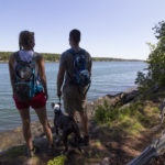 HARPSWELL, Maine -- 07/02/17 -- BDN Outdoor reporter Aislinn Sarnacki and her husband, Derek Runnells, stand at a viewpoint with their dog, Oreo, on July 2, while hiking in Devil's Back Trail Area in Harpswell. (Aislinn Sarnacki | BDN)