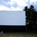 Kids stroll under the big screen at the Prides Corner Drive-In as night falls in Westbrook, Aug. 30, 2013.