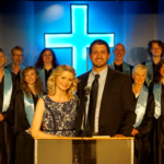 "Dustin Whitehead as Pastor Paul and Ali Fitzpatrick as his wife, Elizabeth, stand before their congregation in ""The Christians."" The play is being performed through July 23 in Somesville by Acadia Repertory Company."