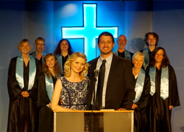 Dustin Whitehead as Pastor Paul and Ali Fitzpatrick as his wife, Elizabeth, stand before their congregation in &quotThe Christians.&quot The play is being performed through July 23 in Somesville by Acadia Repertory Company.