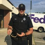 Officer Travis Barnies of the Auburn Police Department holds a snake caught in a car Tuesday.