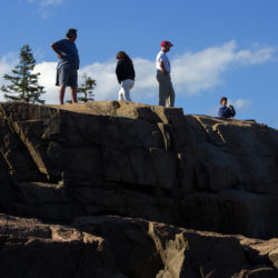 People climb rocks to get a better vantage point of Thunder Hole in Acadia National Park.