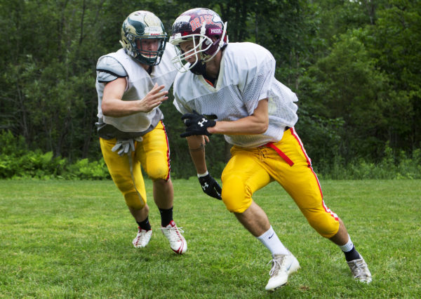 Maine Central Institute's Josh Buker (right) runs past his teammate attempting to block during a drill as part of practice at Foxcroft Academy for the East team as part of the Maine Shrine Lobster Bowl Classic slated for later this week.