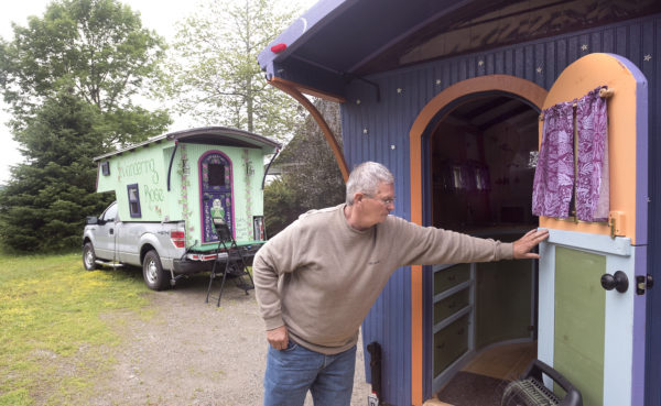 John Kaznecki of South Thomaston opens the door to a camper he built for himself. Pat Guerard of Portland, Connecticut, has spent the past year touring the country in her truck-mounted &quotGypsy caravan&quot she named Wandering Rose (background).  The caravan was also constructed by Kaznecki.