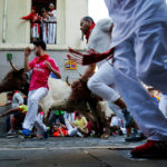 A runner dodges one of the steers that runs with the bulls, during the sixth running of the bulls, at the San Fermin festival in Pamplona, Spain, July 12, 2017.