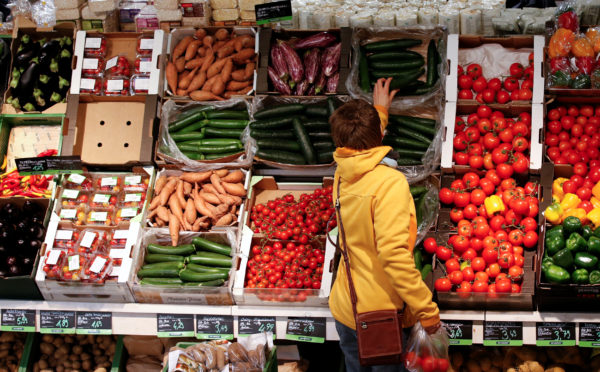 A woman checks vegetables at a supermarket.