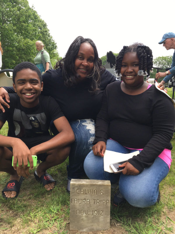 Jaymes Richardson (from left), Lajuani Williams and India Wooding, descendants of Malaga who live in Connecticut, kneel in front of their relative's gravestone.