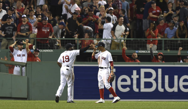 Boston Red Sox right fielder Mookie Betts (right) congratulates center fielder Jackie Bradley Jr. after Bradley robbed New York Yankees right fielder Aaron Judge of a home run during the eighth inning at Fenway Park in Boston on Sunday night.