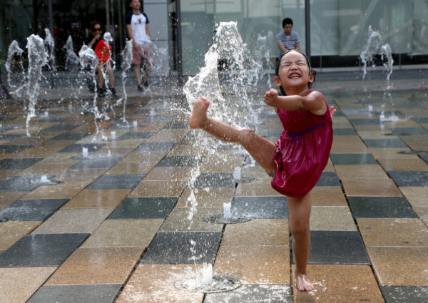 A child plays in a water fountain to cool off on a hot day in Beijing, China, July 12, 2017.