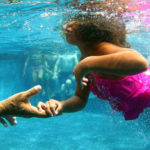 """""""Swim to me, Kelsey,"""" Conrad Cooper, left, says while holding out his hand to Kelsey Atlas, 7, July 18, 2012."""