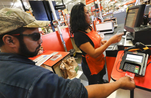 A man inserts his debit card, equipped with an EMV chip, into an EMV reader while making a purchase at a Home Depot store in Burbank, California, Sept. 23, 2015.