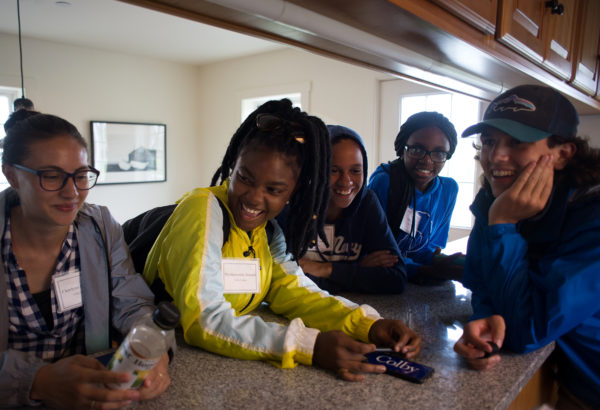 Incoming freshmen at Colby College Charlyna Gonzalez, Mackjeannie Joseph, Nicole Byrd, Chioma Akali, and Connor Wilson (left to right) hang out together in the kitchen of the building where they stayed on Allen Island for four days as a part of the Colby Achievement Program in the Sciences.