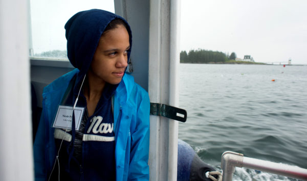 Nicole Byrd from Michigan watches out the cabin door of a boat as she rides back to the mainland from Allen Island where she spent four days with 19 students and faculty members from Colby College. Byrd was selected to participate in the Colby Achievement Program in the Sciences.