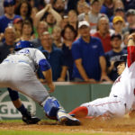 Toronto Blue Jays catcher Russell Martin tags out Boston Red Sox right fielder Mookie Betts at home plate during the seventh inning at Fenway Park in Boston on Monday night.