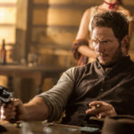 """Chris Pratt as Josh Faraday holds a gun in one hand and a tobacco product in the other in the PG-13 movie """"The Magnificent Seven."""""""