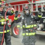 Ellsworth Fire Lt. Gary Saunders washes down a firefighter on Thursday, May 2, 2013, in a demonstration of how the department attempts to rid turnout gear of soot, smoke and dust that contain dangerous chemicals.