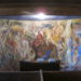 The interior of the South Solon Meeting House, an 1840s building that was transformed in the 1950s with massive interior frescoes painted by acclaimed American modern artists. This mural is by Ashley Bryan.