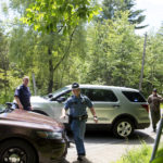 Maine State Police officers go to their vehicles at a road block on Russell Road in Madison, where Somerset County sheriff's deputies shot and killed a man suspected of shooting four people, July 5, 2017.