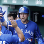 Toronto Blue Jays first baseman Justin Smoak (right) is congratulated after hitting a home run against the Boston Red Sox in the fifth inning at Fenway Park in Boston on Thursday.