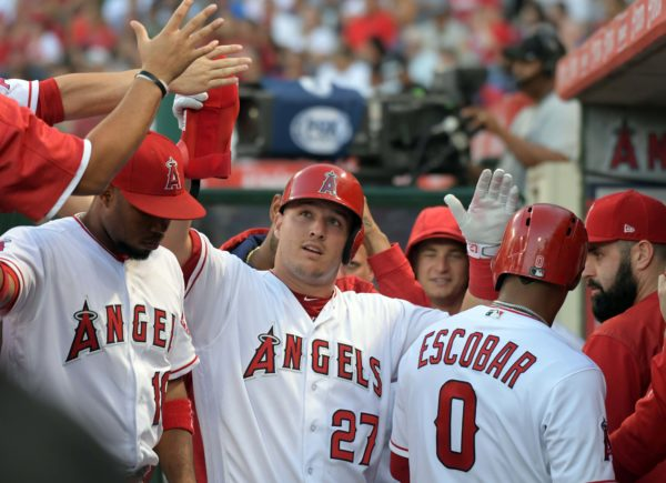Los Angeles Angels center fielder Mike Trout (27) is congratulated by teammates after scoring in the third inning against the Boston Red Sox.