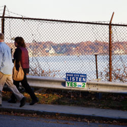 Pedestrians pass by a view of Portland Harbor on Fore Street in Portland, Nov. 3, 2015.