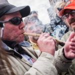 Robert Chute (right) and a man who only gave his name as Michael L. light up a large joint in Portland's Monument Square on April 20, 2017.