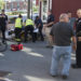 Rescue workers attend to an unidentified victim as Bangor police and witnesses look where on Cross Street a motorist sped after hitting a bicyclist in downtown Bangor on Tuesday.