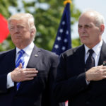 U.S. President Donald Trump (left) and U.S. Department of Homeland Security Secretary John Kelly hold their hands over their hearts for the U.S. National Anthem as they attend the Coast Guard Academy commencement ceremonies on May 17, 2017.