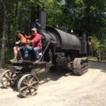 Volunteer operators take a few passengers on a ride Saturday aboard the steam-powered Lombard log hauler on Saturday  at Heavy Metal Day at the Maine Forest and Logging Museum at Leonard's Mills. Built in 1910, it took 150 volunteers and University of Maine students decades to restore the machine to working order.