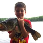 Landon Martin, 5, of Bangor holds the big bass his father, Free Martin, caught in a Hancock County pond recently.