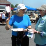 Dr. Ann Hamilton of Bangor on left, with Maine AllCare volunteer Lanny Anderson from Deer Isle, discussing the benefits of Medicare for All type of system at the Fishermen's Day event in Stonington.