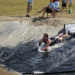 "Ryan McLaughlin dives through the ""Slip, Slide and Die"" obstacle and into a pit of mud during the Tough Mountain Challenge at Sunday River July 21, 2012."