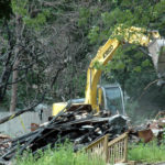 An excavator clears debris at the Reed Mansion site on Glidden Street in Waldoboro the afternoon of Monday, July 10.