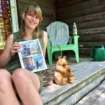 """Writer Katy Kelleher with her new book """"Handcrafted Maine"""" sits on her stoop next to a bear sculpture by Ray Murphy, one of 22 makers featured in her book."""