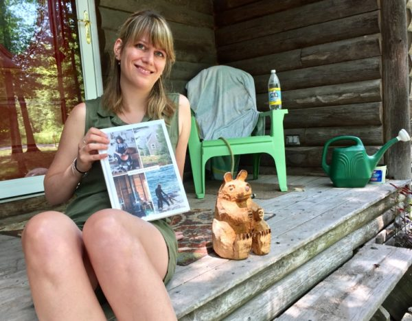 Writer Katy Kelleher with her new book &quotHandcrafted Maine&quot sits on her stoop next to a bear sculpture by Ray Murphy, one of 22 makers featured in her book.