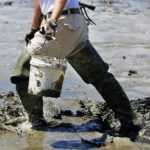 Cameron Brann trudges through the mud looking for a spot to dig for bloodworms in a mudflat on the Jordan River in Lamoine. Brann, who is still new to digging, digs year-round and hopes to dig around 500 worms a day.