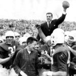 Coach Ara Parseghian salutes the Dyche stadium crowd with the game ball as his Northwestern Wildcats carry him off the field following their 21-0 victory over Ohio State on Nov. 1, 1958.