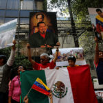 Supporters of Venezuelan President Nicolas Maduro hold up pictures of Venezuela's late president Hugo Chavez, during an event in favor of Venezuela's Constituent Assembly election, outside Venezuela's embassy in Mexico City, July 30, 2017.