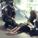 New York police officer Larry DePrimo gives a homeless man a pair of boots and socks in Times Square in this November 14, 2012 handout photo courtesy of Jennifer Foster.
