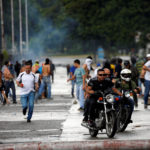 Demonstrators run and ride their motorcycles near Fuerte Paramacay military base during clashes with security forces in Valencia, Venezuela Aug. 6, 2017.