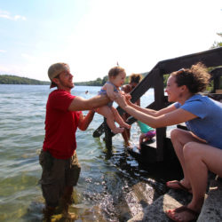Danielle and Ray Ruby of Portland play with their 8-month-old daughter, Eloise, at the beach of Lake St. George State Park on July 22, 2017, in Liberty.